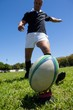 Player kicking rugby ball on grassy field