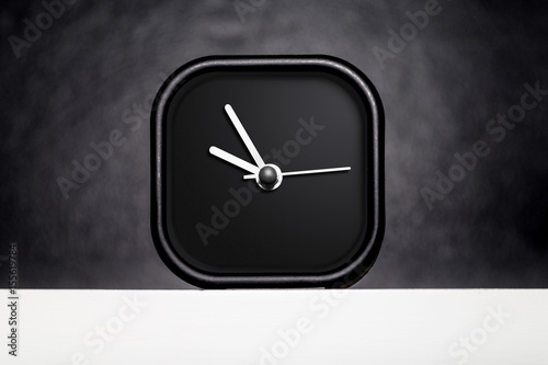 Close up modern black square table clock on white shelf at black wall Poster