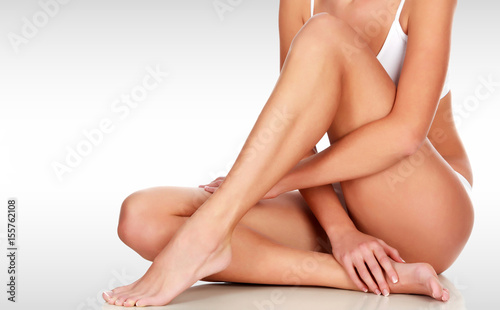Leinwandbild Motiv Young woman with slim body, smooth and soft skin against a grey background with copyspace