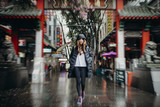 Sydney, Australia - February 25, 2017: Woman crossing the Chinatown arch in Sydney, Australia.