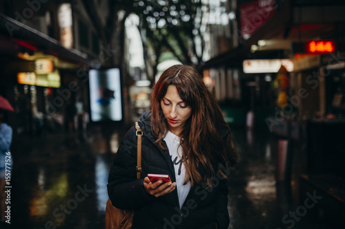 Poster Sydney Tourist searching for restaurant with mobile phone in Chinatown neighborhood in Sydney, Australia.