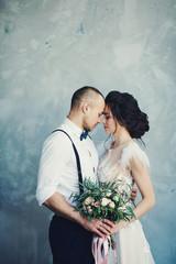 The bride and groom hugging in studio