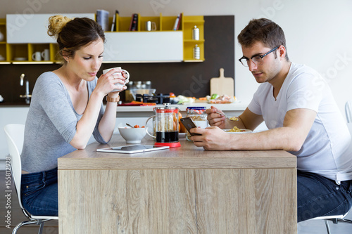 Poster Beautiful young couple using digital tablet and smartphone while enjoying the breakfast