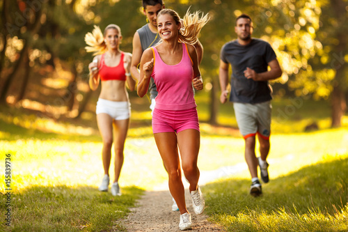 Fotobehang Hardlopen Young female jogging with her friends at the park.