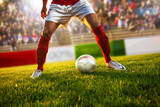 Soccer player with red socks in dribble position..Stadium is blurred behind him. - 155843737