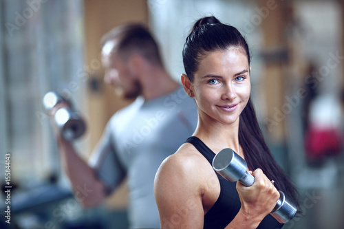 Couple doing workout on fitness machine at gym.