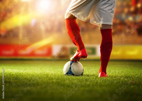 Soccer player with red socks in dribble position..Stadium is blurred behind him.