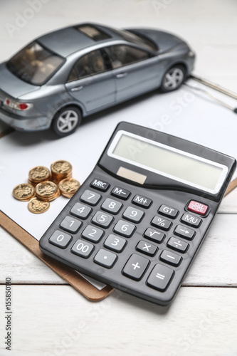car model,calculator and coins on white table - 155850140
