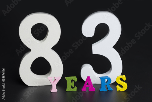 Poster Letters and numbers eighty-three years old on a black background.