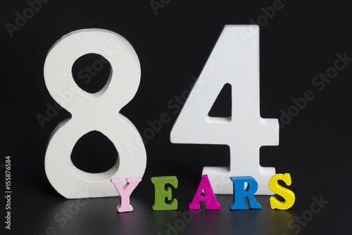 Poster Letters and numbers eighty-four on a black background.