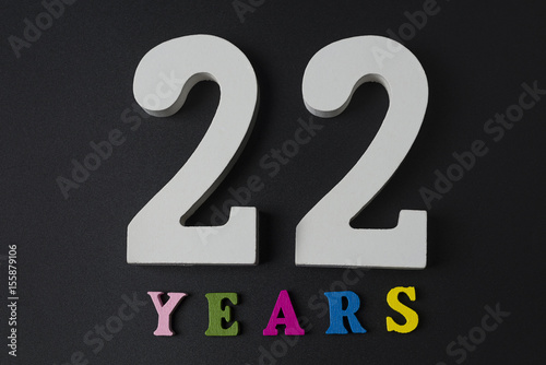 Poster Letters and numbers twenty-two on a black background.
