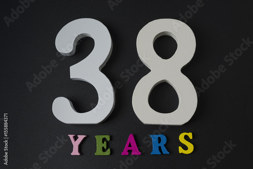 Poster Letters and numbers thirty-eight years on a black background.