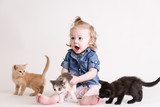 Cute toddle girl plays with baby kittens - 155893145