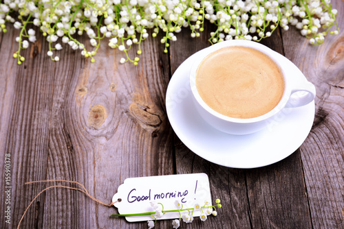 Fotobehang Lelietjes van dalen Cup of coffee and a paper tag with the inscription good morning