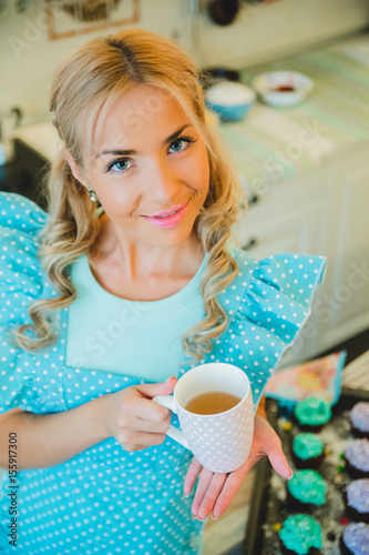 young blond woman drinking tea in the kitchen Poster