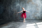 girl ballerina in red tutu doing exercise