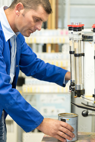 Worker using paint mixing machine Poster