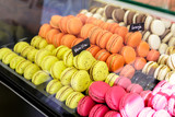 Colorful macarons dessert with a signs saying: Orange and vanilla.