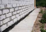 Waterproofing and insulation unfinished house foundation wall. Waterproofing house foundation with bitumen membrane. - 156188769