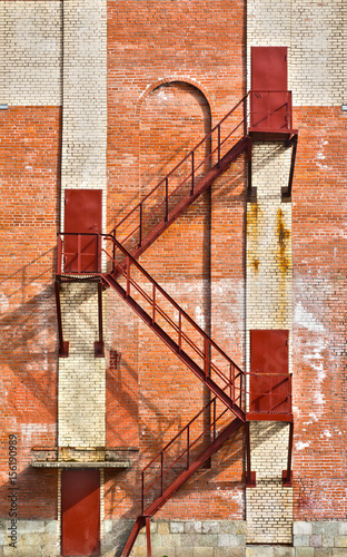 Fototapeta brown staircase and doors on old brick wall