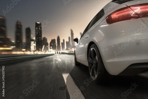 Auto fährt bei Abenddämmerung auf eine Stadt zu
