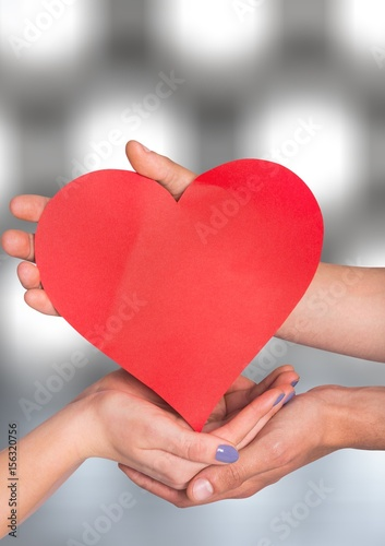 Hands holding heart with sparkling light bokeh background