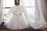 Little white dress on hanger near window - 156336344