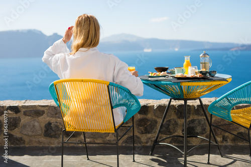 Woman enjoying morning in luxury hotel in Santorini Poster