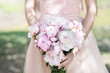 Woman holding in hands wedding bouquet with peonies