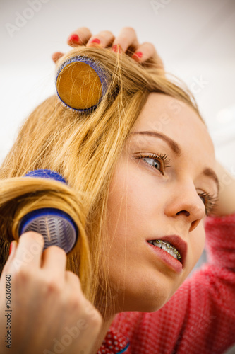 Woman curling her hair using rollers © Voyagerix