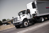 Fototapety White semi truck and stainless steel refrigerator trailer on highway
