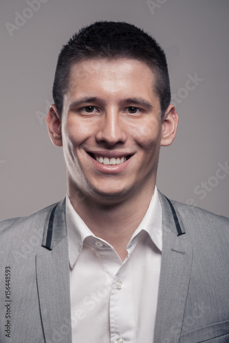 one young man, upper body, formal clothes, head face headshot smiling
