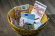 Leinwanddruck Bild - basket with money from donations