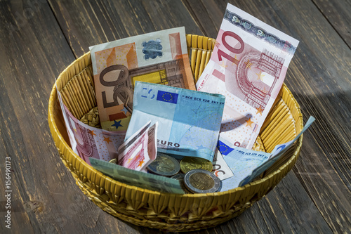 Leinwanddruck Bild basket with money from donations
