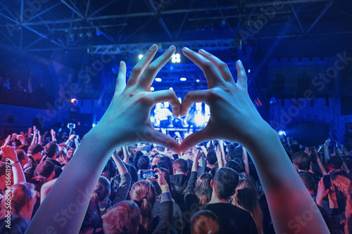 The silhouettes of concert crowd in front of bright stage lights Poster