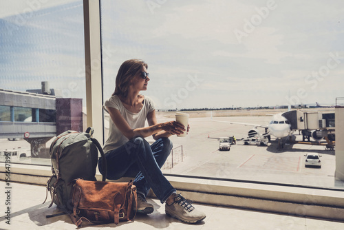 Young woman in the airport, looking through the window at planes and drinking co Poster