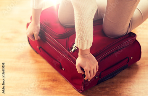 close up of woman packing travel bag for vacation Plakat