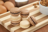 Chocolate and Vanilla Macarons with Ingredients on Striped Board