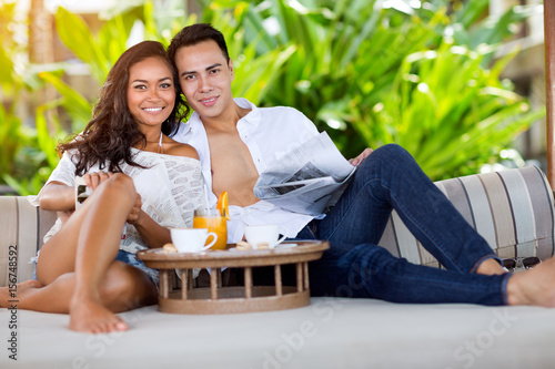 Poster handsome couple in tropical resort.
