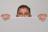 Man peering over office cubicle - 156763769