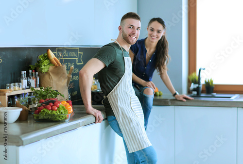 Poster Beautiful young couple is having fun in kitchen at home