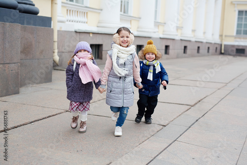 Joyful friends in warm clothes looking at camera and running