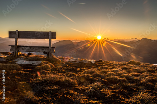Foto op Canvas Ochtendgloren Berglandschaft mit Sitzbank während dem Sonnenaufgang