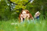 frau liegt auf einer grünen wiese und hört musik - 156909391