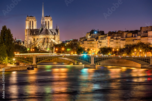 Notre Dame de Paris Cathedral, Seine River and the Sully Bridge at twilight. Summer evening on Ile Saint Louis, 4th Arrondissement in Paris. France