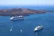 Zwei Kreuzfahrtschiffe ankern im blauen Meer im  Krater des erloschen Vulkans von Santorin.
