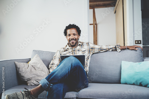 Poster Bearded smiling American African man using tablet for video conversation while relaxing on sofa in modern home