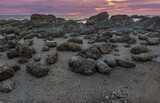 Rocks on the beach with sunset sky.
