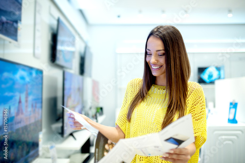 Beautiful young woman reading a brochure. Buying new tv set at the tech store.