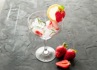 cocktail made from Strawberries and rosemary ice cubes into the glass